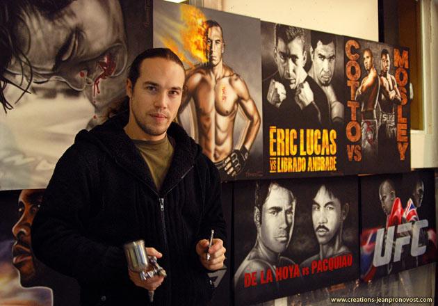 Voici l'artiste Jean Pronovost tenant ces instruments de travail devant quelques une de ces peintures.