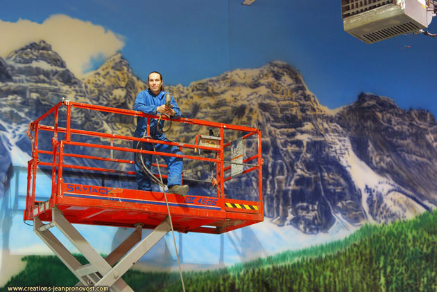 Airbrush painter artist Jean Pronovost in front a large scale mural